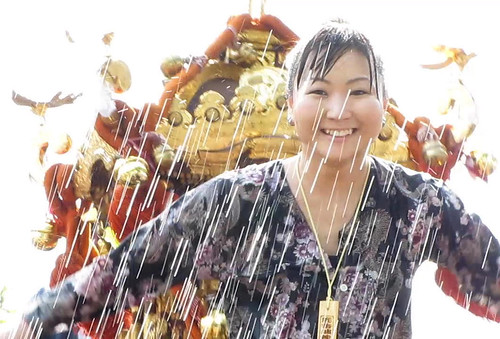 Youg girl atop Omikoshi portable Shinto shrine drenched in water being splashed at the pararde, Powell Street Festival 2010 where Japanese tradition meets new expression in Vancouver Canada