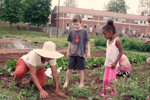 Lucia Daugherty & kids in the Pisgah View Community Peace Garden (by: Jonathan Welch, Mountain Xpress)