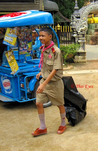 cute, young Thai boy scout collecting garbage