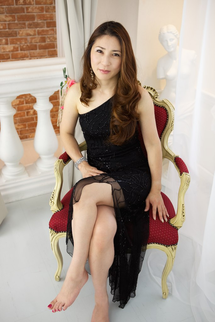 Japanese woman sitting in red and gold chair in black dress, one hand in lap one on chair