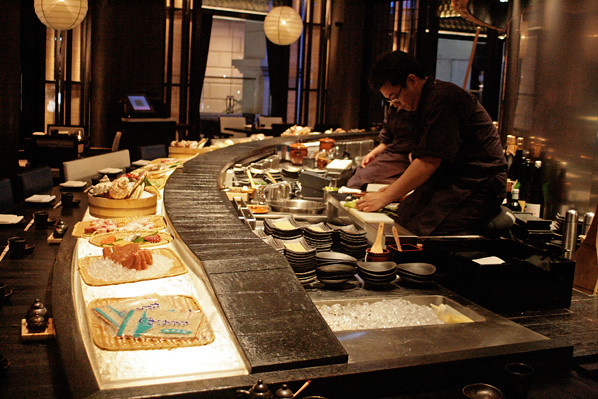 The restaurant's main dining area is a circular ring, and the chefs kneel elevated before the grill