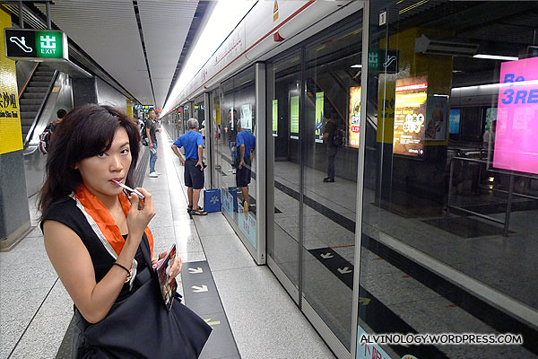 Rachel applying lipstick while waiting for train