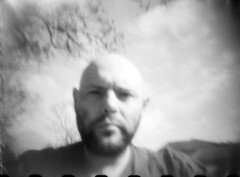 self portrait- handheld homemade pinhole (bradley gaskin) Tags: camera portrait sky bw blur film self 35mm diy serious australia pinhole homemade handheld adelaide claude procrastination why sa bother jacaranda frown bastard grumpy perplexed bearded oof backtowork populist homedeveloped scannedfromnegative crankypants canoscan8800f haveashave expiredfujineopanssilfosol319for5mins20°c youcandoeeeeet refertagreprocrastination