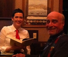 Cathi Murphy, bartender at Johnny Foley's Irish House, reading a copy of What We See. Pictured with Gary Gumpert, President of the Urban Communication Foundation.