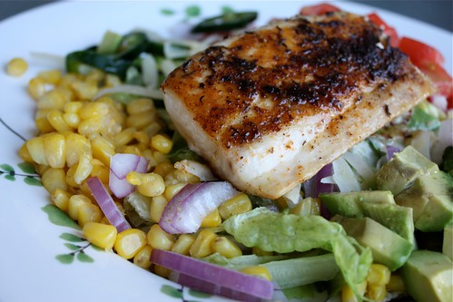 plate of corn, red onions, avocado, jalapeno peppers, and diced tomatoes with a piece of blackened fish on top
