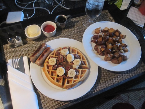 Waffles with pecan butter, banana, sausages, potatoes