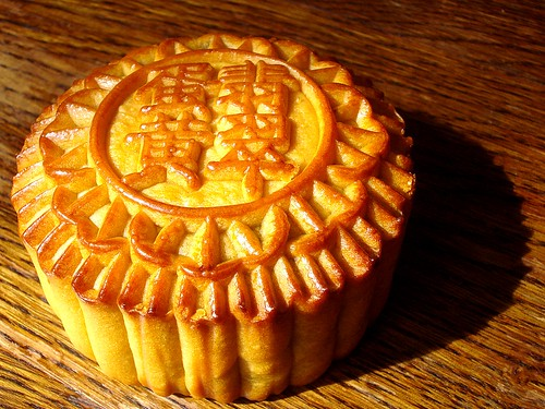 A round, golden-brown, raised-pastry pie with fluted edges and the Chinese characters 翡翠/蛋黃 embossed on top.