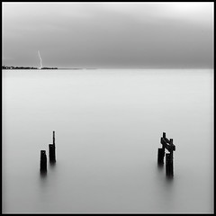 bolt of minimalism (Mark Emirali) Tags: ocean longexposure light sunset sea newzealand sky cloud sun seascape storm motion blur art texture beach nature water rain night clouds canon square landscape mood view harbour wideangle auckland nz canon5d poles lightning aotearoa tone onehunga copyrighted pleasedonotusewithoutmypermission maloe4 5dmkii maloephoto maloephotography markemirali markemiraliphotography
