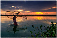 throw (Soumya Bandyopadhyay) Tags: sunset sky lake fish net water colors clouds landscape fisherman dusk wide gradnd pentaxk200d pentax1855mmii