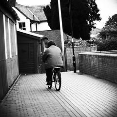 Ride (ant_sk) Tags: street bw white man black bike square lens 50mm ride candid olympus om f18 vignetting zuiko e510