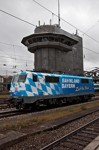 111 017 fährt am Stellwerk München Hbf vorbei