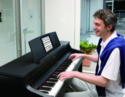 An adult piano student works on the Roland digital piano.