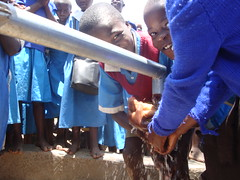 Happy and smiley students of Eshikhoni primary school feeling clean water during hand over ceremony