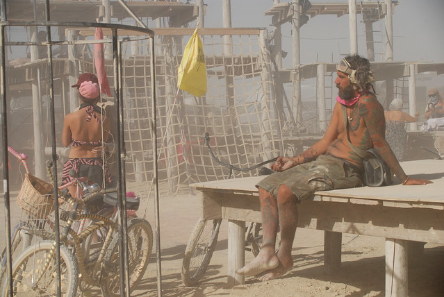 A tattooed man sits on a wooden platform in the desert at Burning Man.