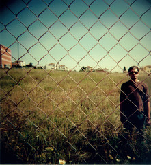 Behind The Wire Fence (josemanuelerre) Tags: flowers blue sky man flores flower building guy verde green field grass sunglasses azul fence landscape stand holga lomo wire flor edificio paisaje cielo campo gafas behind hombre valla cesped tipo alambre detrs to depie