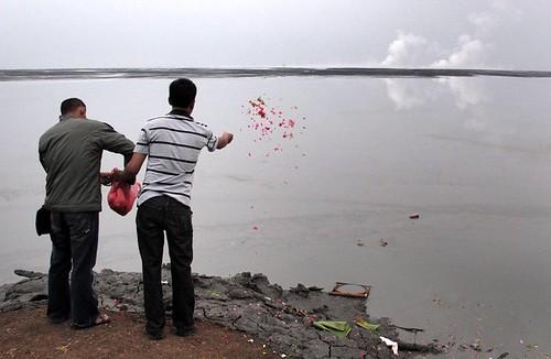 Dua warga korban lumpur panas Lapindo, menaburkan bunga ke arah lautan