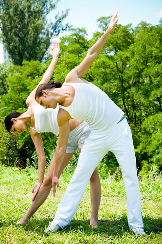 Young happy couple doing fitness exercises together outdoors