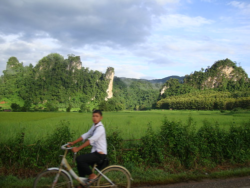 Laos boy bicycles to school