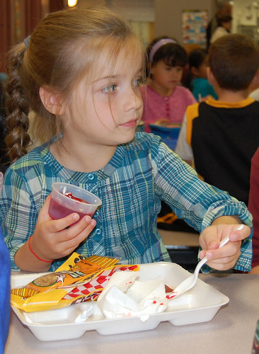"First-grader Cassidy Stone clears her tray of soy nuts, whole wheat pizza stick, broccoli and jello, saying ""the food tastes good."""