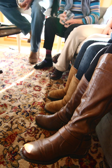 Legs and feet in front of couches and chairs.