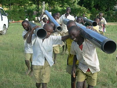 Pupils of Ebusyubi Primary School helping bringing PVC pipes close to the site