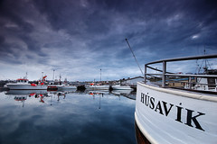 Hsavk (Micha Sacharewicz) Tags: ocean travel blue sea sky mountains reflection water sign clouds port landscape boats bay harbor pier boat iceland ship cloudy harbour name side ships letters calm arctic 1224mmf4g portfolio nikkor sland inscription prow hsavk skjlfandi 00006279