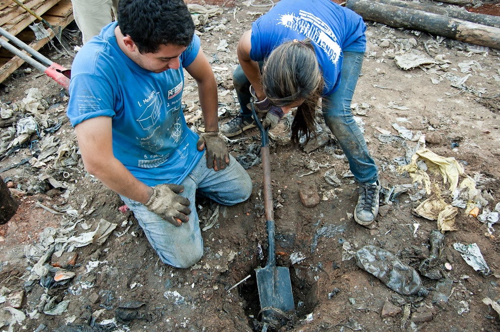 Voluntarios sufren todo el esfuerzo físico para poder cavar pozos en el irregular terreno de la zona de Cateura donde van a construir las casas, el suelo está formado por la mezcla de basura y tierra que dificultan la tarea. (Elton Núñez - Asunción, Paraguay)