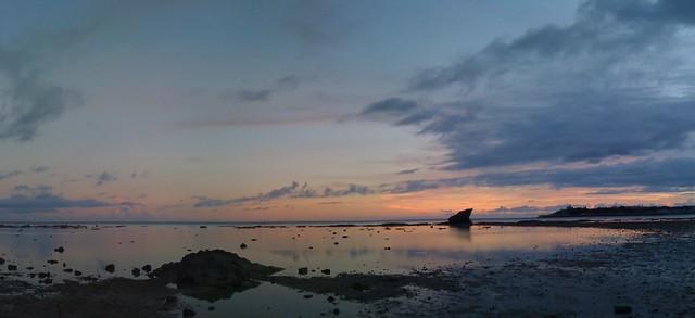 玉城(たまぐすく)の夕暮れ海岸パノラマ。風も波もない。静かだ …