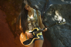 Teenage rocker on large rocks (KnightWolf Photography) Tags: red musician music woman playing black girl beautiful fashion rock female hair fun outdoors student model long artist guitar background young band culture jazz style happiness pop boulders rocker singer instrument learning teenager string casual cheerful guitarist teenage