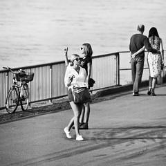 (city/human/life) Tags: camera city summer people urban blackandwhite bw sun sunlight water bike fence river flow glasses licht nikon candid sommer paar august sw zaun fluss dsseldorf rhine rhein 2009 fahrrad weg chl rheinufer d90 sonnenlicht kameras rheinuferpromenade schwarzweis nikond90 promeade cityhumanlife