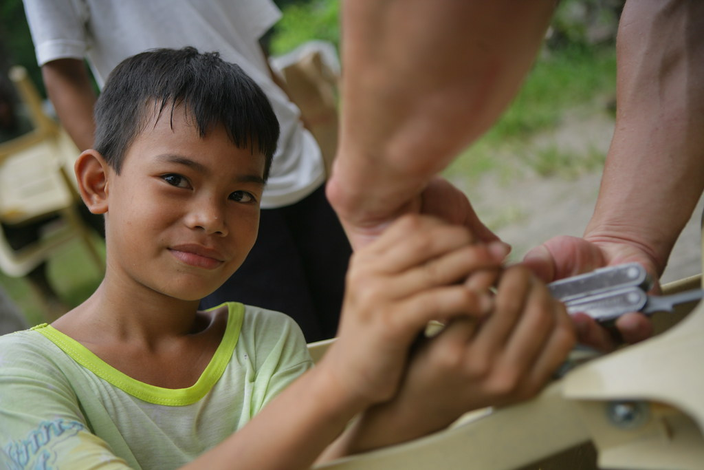 Filipino boy helps Marines assemble school furniture