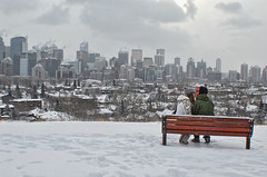 Grey skies (shicoles) Tags: city trees winter boy sky white snow canada cute love boyfriend girl skyline clouds d50 bench print grey nikon kissing girlfriend couple skies sitting ground canadian relationship snowing exchange
