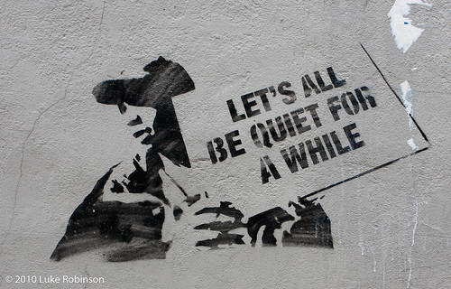 stencil graffiti of a young man holding a sign that reads, let's all be quiet for awhile.