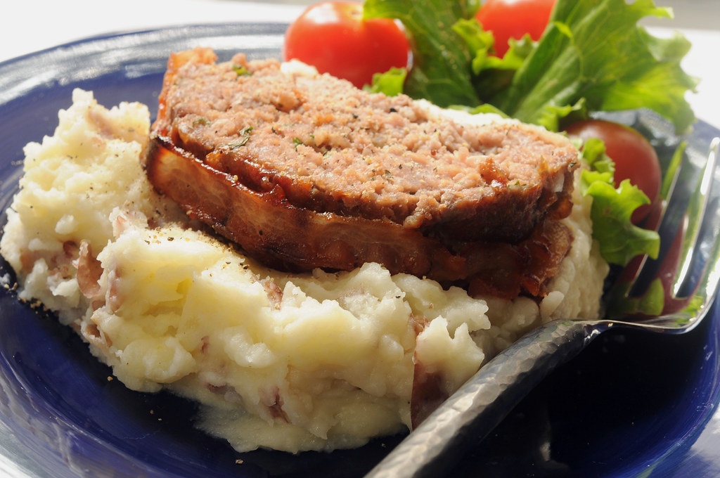 bacon wrapped meatloaf slices on mashed potatoes