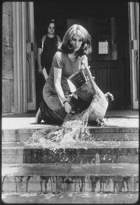 A black-and-white photograph of Mierle Ukeles pouring a mop bucket of water down the stone steps of an art gallery