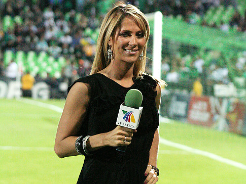 a picture of Ines Sainz. She is tan and had blonde hair. She is wearing a black dress and smiling while standing on a green athletic field.
