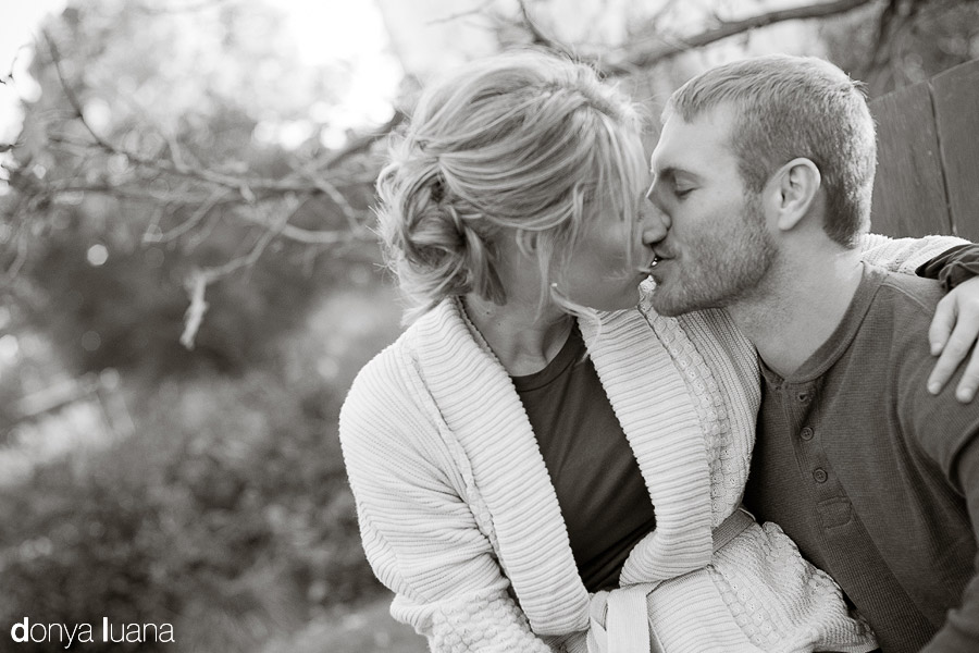 Kissing couple on chair at St. Olaf College in Northfield Minnesota for portraits