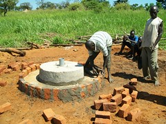 A man put mortar between bricks to form the apron