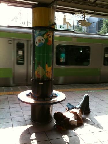 朝の原宿駅のホームで寝てる人