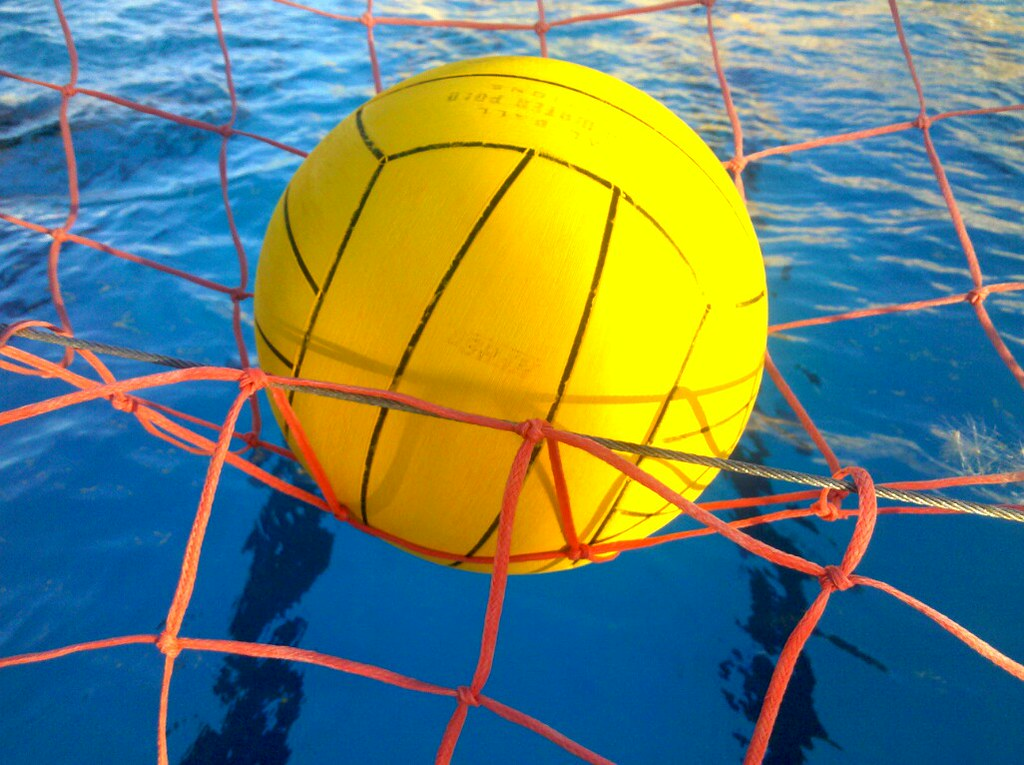 Water polo ball sitting on top of an orange net with blue swimming pool behind it.