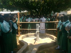Rev.Father reading a verse from the bible before commissioning of the well at Emalindi Girls Sec.School during hand over ceremony