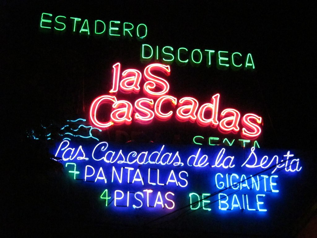 The large neon sign of Las Cascadas Discoteca on La Sexta advertises 7 large video screens and 4 dance floors.
