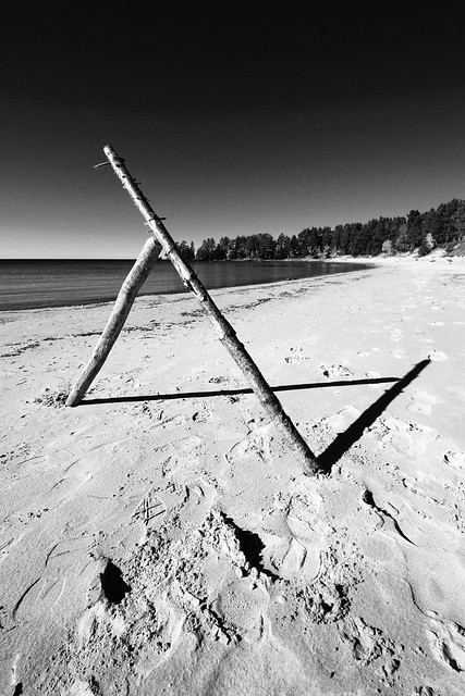 Two sticks resting against each other on the beach, in black and white.