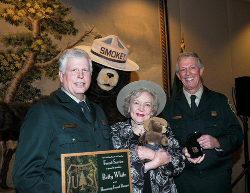 Actress Betty White holds the certificate and Forest Ranger badge presented to her by US Forest Service Chief Tom Tidwell (left) and Deputy Chief Hank Kashdan, as Smokey Bear looks on. White was named an Honorary Forest Ranger in a ceremony at the Kennedy Center for the performing Arts in Washington DC November 9. (US Forest Service photo by Karl Perry)