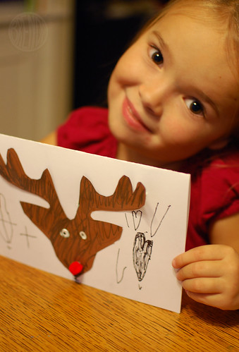 child smiling while holding handmade reindeer Christmas card