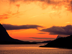 Midnattssol över vatten och berg