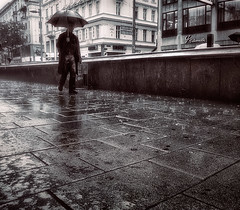 Walk Alone (Mikko Lagerstedt) Tags: vienna wien life road street blue light shadow red urban streets color green art nature water colors beautiful field rain umbrella suomi finland dark landscape photography austria photo colorful mood alone view darkness graphic natural image photos unique fineart fine perspective award atmosphere finnish raining mikko 2010 latyrx intherain d90 nikond90 nikkor18105mm finnishphotography lightsplease mikkolagerstedt lagerstedt