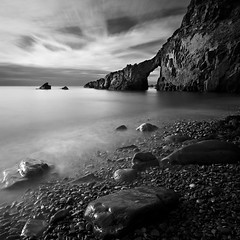 window on the rock (s k o o v) Tags: longexposure sea bw beach clouds rocks arch explore dodge sark 1020 2010 explored portdumoulin 450d nd110 rocksrocksrocks skoov