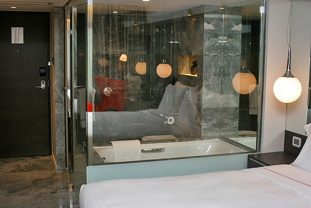 Glass bathroom partitions not only tease, but make the room look even bigger