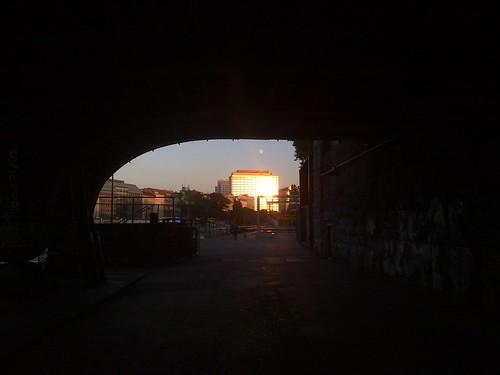 An einem Bürhaus am Donaukanal reflektierende Sonne von unter einer Brücke aus.